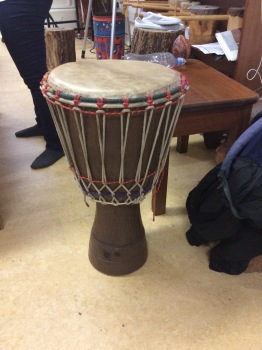 This is a djembe. The top is made of goat skin, and you tighten the top, or the head with the basket of strings around the body of the drum. They are usually handmade in Ghana