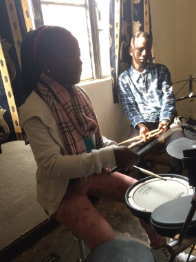 Leontine teaching new rhythms on the electric drum set