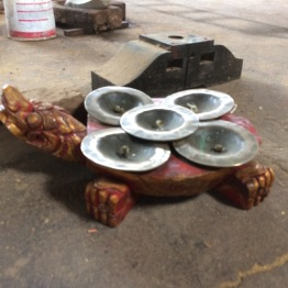 The turtle is seen as the foundation of Balinese religion and culture. The cymbals here are placed on a turtle and keep the beat of the ensemble. So they are the foundation of the ensemble