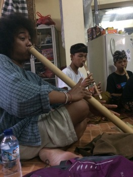 Balot playing along with the children with a meter long wood flute